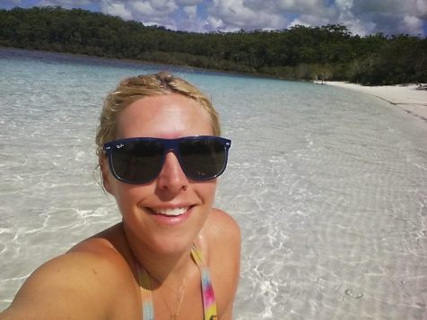 A girl sits in the crystal clear waters of Lake McKenzie, Lake McKenzie, Fraser Island, Australia
