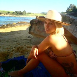 A girl sits on a deserted beach with a sunhat