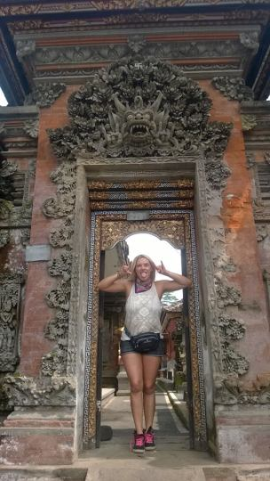 girl standing in ornate temple doorway in Bali