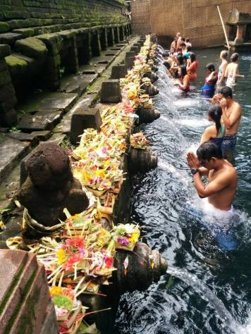 People bathing in the holy spring water of Titra Empul