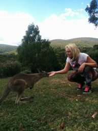 A girl feeds a baby kangaroo or joey in Australia