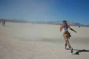 A girl chases a dust devil at burning man