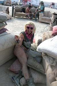 a girl laughing on the ground at burning man