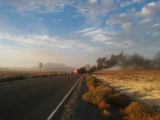 A deserted RV burns on the road side of Nevada route 447