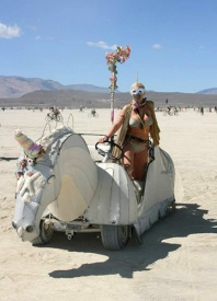 A girl riding a unicorn art car at burning man
