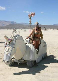 A girl riding a unicorn art car at burning man