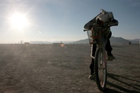 Girl sleeping on bike as sun rises at burning man