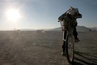 Girl sleeping on bike as sun rises at burning man