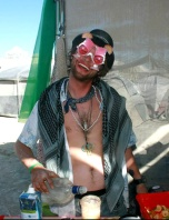 A man wears silly sunglasses and serves drinks at burning man
