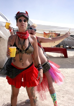 a man photo bombing a friend at burning man