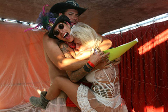 Two brides and their priest hug after just being married at Burning Man