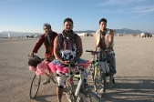 3 men on bikes at burning man in tutu's