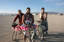 3 men on bikes at burning man in tutu's