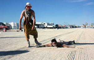 man on dusty ground naked at burning man