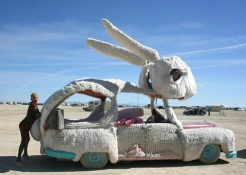 Man standing next to bunny inspired art car at Burning Man