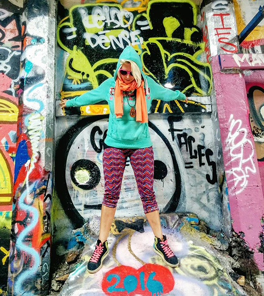 girl in front of colorful graffiti wall