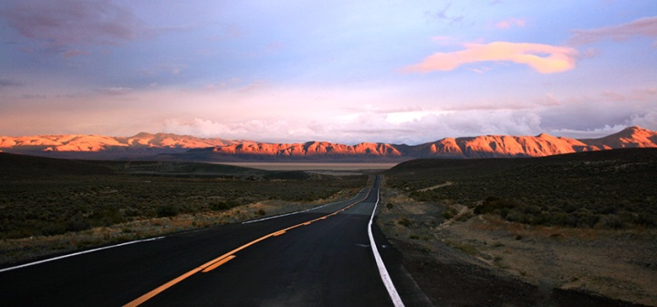 Open road with mountains in distance sunset