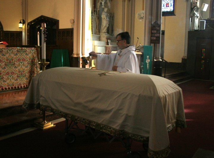 priest blessing a casket at a funeral catholic